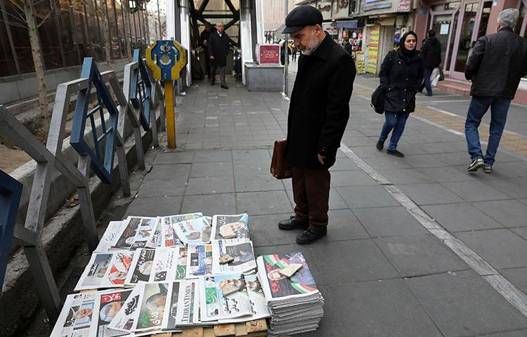 A man reads newspapers in Tehran, Iran, on January 4, 2020. The country recently banned all newspaper printing and distribution, citing fears of spreading COVID-19. (AP/Vahid Salemi)