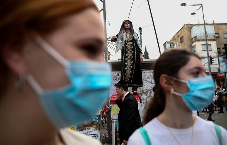 Ultra-Orthodox Jewish girls wear face masks during celebrations of the Purim festival in Bnei Brak, Israel, on March 10, 2020. CPJ recently spoke with Laura Adkins, an Orthodox Jewish editor at the Jewish Telegraph Agency. (AP/Oded Balilty)
