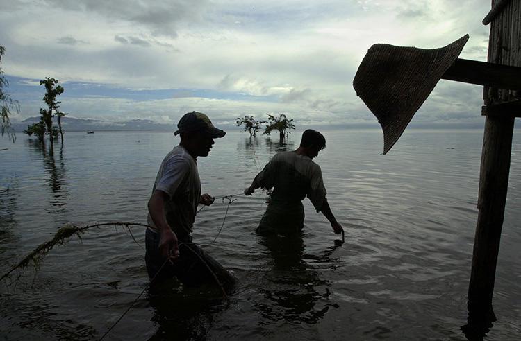 Pescadores en medio de sus labores en el lago Izabal, Guatemala, en 2002. Los periodistas que cubren distintas problemáticas de la región, como el impacto de la contaminación industrial, son objeto de amenazas y demandas judiciales. (AP/Jaime Puebla)