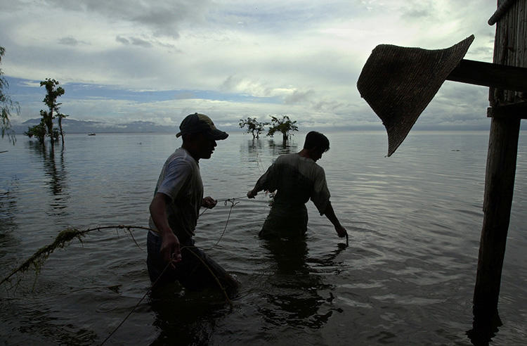 Fishermen work in Guatemala's Lake Izabal in 2002. Journalists covering issues in the region, including the impact of industrial pollution, face threats and legal action. (AP/Jaime Puebla)