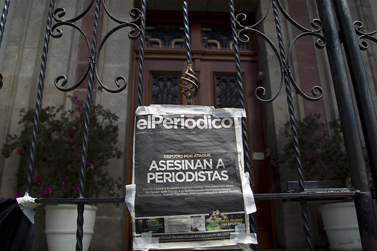 The front page of the newspaper elPeriodico de Guatemala that reads, in Spanish, 'Journalists killed' hangs on a gate at the Presidential House during a protest in March 2015 over the killing of journalists Danilo Lopez and Federico Salazar. (AP/Moises Castillo)