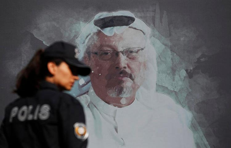 A police officer is seen near a picture of slain Saudi journalist Jamal Khashoggi in Istanbul, Turkey, on October 2, 2019. Today, Turkey indicted 20 Saudi nationals in Khashoggi's killing. (AP/Lefteris Pitarakis)