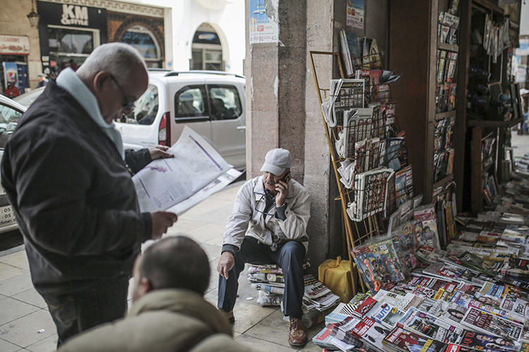 A man reads a newspaper at a stall near the Medina of Rabat, Morocco, on March 16, 2017. Morocco, Yemen, Oman, and Jordan recently ordered newspapers to cease production, citing fears of spreading the COVID-19 virus. (AP/Mosa'ab Elshamy)