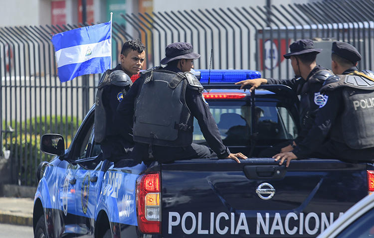 National Police officers are seen in Managua, Nicaragua, on August 24, 2019. National Police have been surveilling and harassing journalist Emiliano Chamorro. (AP/Alfredo Zuniga)