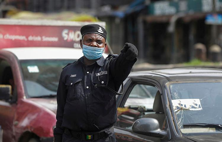 A police officer is seen at a roadblock in Lagos, Nigeria, on March 31, 2020. The Nigerian government recently imposed restrictions on journalists' movement and access to stem the COVID-19 pandemic. (AP/Sunday Alamba)