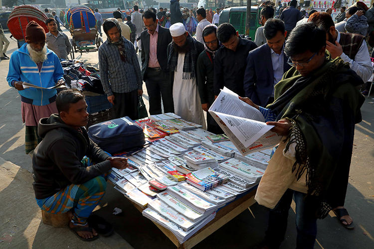 People read newspapers in Dhaka, Bangladesh, on January 30, 2019. Journalist Shafiqul Islam Kajol recently went missing after he was named in a criminal defamation suit. (Reuters/Mohammad Ponir Hossain)