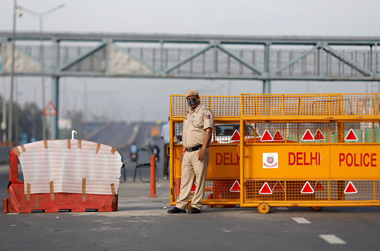 A police officer stands at a barricade in New Delhi, India, on March 23, 2020. Police in New Delhi and Hyderabad recently assaulted journalists for allegedly violating the cities' lockdowns. (Reuters/Adnan Abidi)