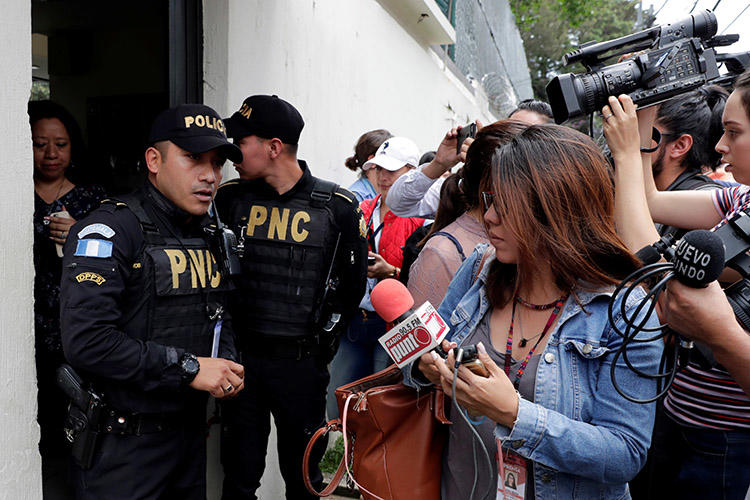 Police and the media are seen outside the Guatemala City offices of the International Commission Against Impunity office (CICIG) in August 2018. The popular U.N.-backed commission helped usher in a decade defined by strong investigative journalism and progress in the fight against Guatemala's endemic corruption (Reuters/Luis Echeverria)