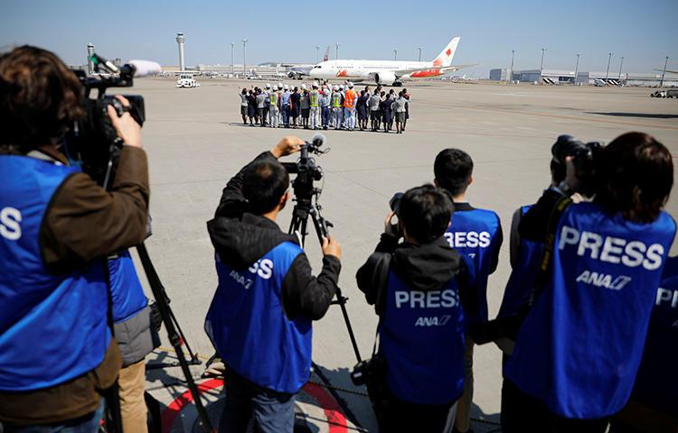 Members of the media watch as the Olympic Flame is transported to Japan, at Haneda international airport in Tokyo on March 18, 2020. CPJ recently joined a call for transparency and press freedom at the Olympics and other major sporting events. (Reuters/Issei Kato)