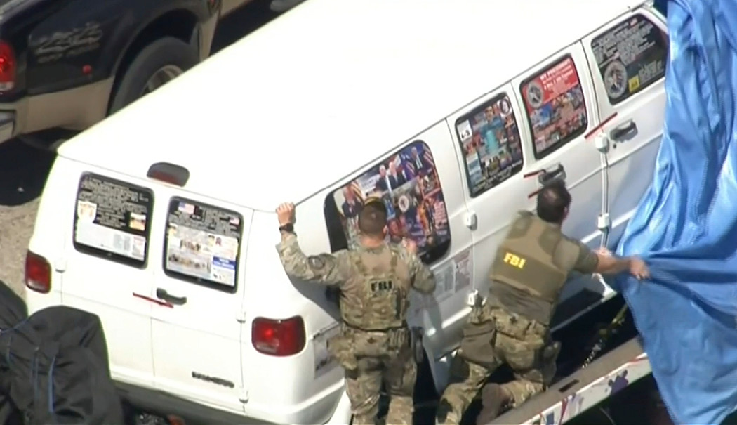 A video frame shows FBI agents on October 26, 2018, pulling a tarp over a van from Plantation, Florida, covered in pro-Trump stickers. The van was investigated in connection with package bombs sent to the CNN newsroom in New York and to other perceived critics of President Trump. (WPLG-TV via AP)