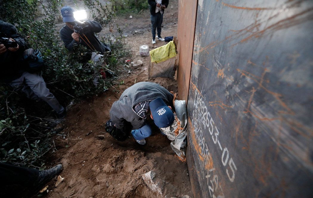 A Honduran migrant crawls through a hole under the U.S. border fence as journalists take pictures, in Playas de Tijuana, Mexico, on December 4, 2018. U.S. Customs and Border Protection monitored some journalists covering migration in a secret database. (AP/Rebecca Blackwell)