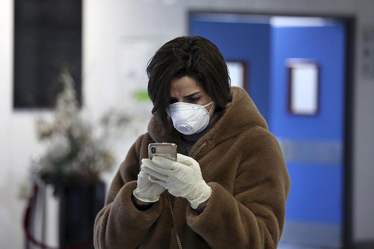 A Lebanese journalist uses her mobile phone as she wears a medical mask and gloves at Rafik Hariri University Hospital in Beirut, Lebanon, on February 22, 2020. (AP/Bilal Hussein)