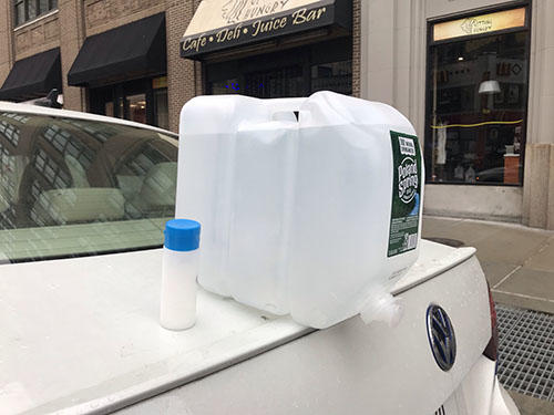 A makeshift sink made by resting a 2.5 gallon water jug with push tap over the edge of photojournalist Angus Mordant's trunk allowing for easy access to hand washing on the job. (Angus Mordant)