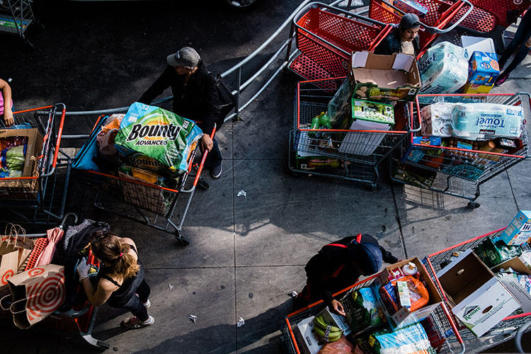 People wait for their rides with carts full of groceries preparing for social distancing at East River Plaza in New York City on March 13, 2020. (Gabriela Bhaskar for The New York Times)
