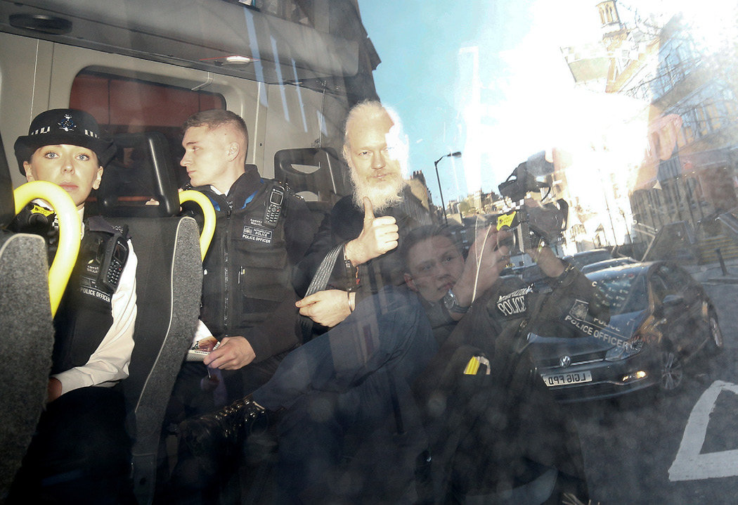 WikiLeaks founder Julian Assange gestures as he leaves the Westminster Magistrates' Court in a police van after he was arrested in London on April 11, 2019. The Trump administration charged Assange under the Espionage Act. (Reuters/Henry Nicholls)
