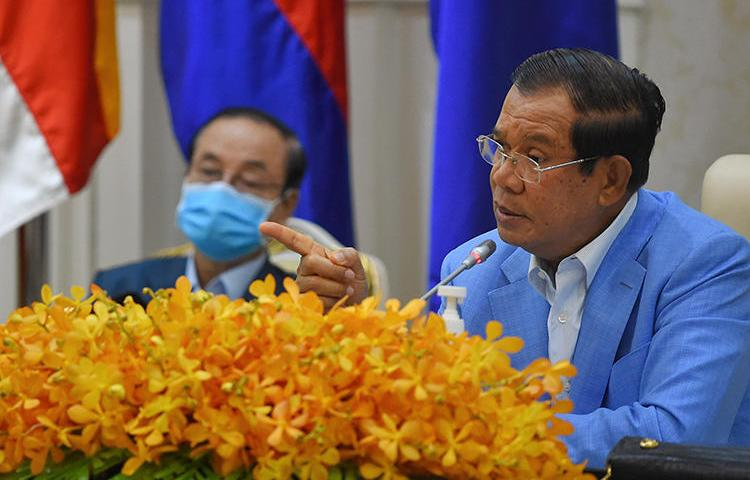 Cambodian Prime Minister Hun Sen (right) is seen during a press conference at the Peace Palace in Phnom Penh on April 7, 2020. Journalist Sovann Rithy was recently detained for publishing quotes from the prime minister. (AFP/Tang Chhin Sothy)