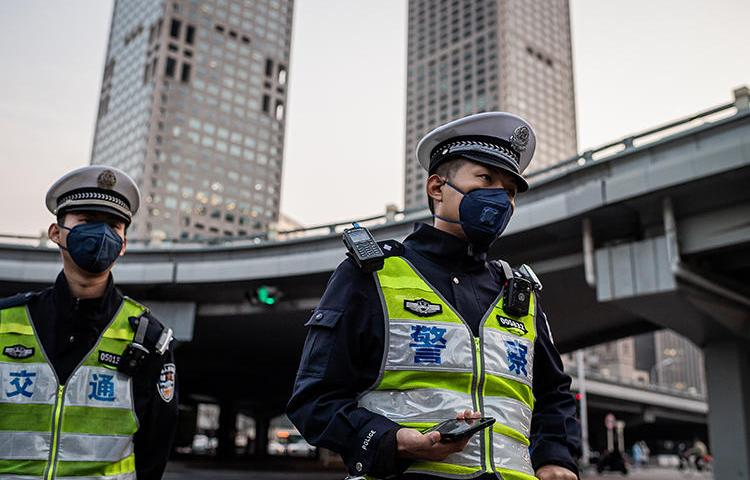 Police officers stand at a street crossing in Beijing, China, on April 7, 2020. Beijing police recently arrested documentary filmmaker Chen Jiaping on subversion charges. (AFP/Nicolas Asfouri)