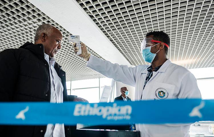 A worker of the Ethiopian Public Health Institute measures a man's temperature in Addis Ababa, on March 17, 2020. Ethiopian police are holding journalist Yayesew Shimelis pending a terrorism investigation. (AFP/Eduardo Soteras)