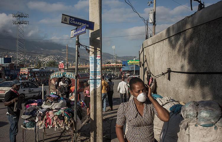 Une femme se promène dans le centre-ville de Port-au-Prince (Haïti), le 26 mars 2020. Huit journalistes ont été agressés récemment en couvrant la pandémie de coronavirus à Port-au-Prince. (AFP/Pierre Michel Jean)