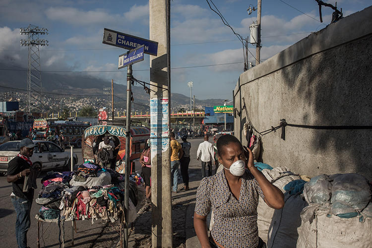 A woman walks in downtown Port au Prince, Haiti, on March 26, 2020. Eight journalists were recently attacked while covering the coronavirus pandemic in Port au Prince. (AFP/Pierre Michel Jean)