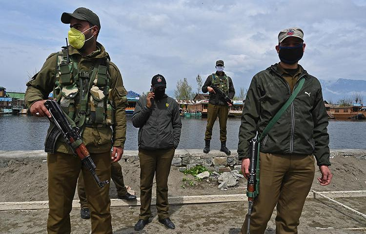 Police officers are seen Srinagar, Indian-controlled Jammu and Kashmir state, on March 31, 2020. Jammu and Kashmir police recently launched an investigation into journalist Gowhar Geelani. (AFP/Tauseef Mustafa)