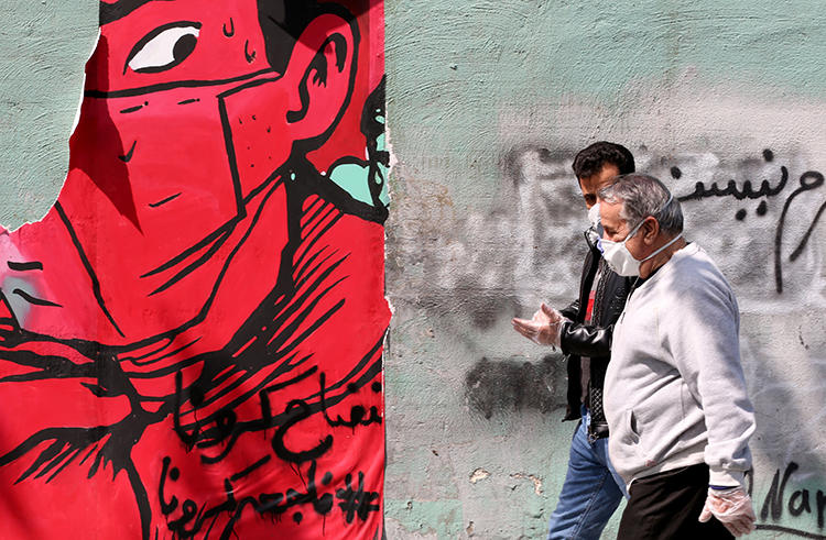 People walk in Tehran, Iran, on April 13, 2020. Two Iranian universities recently filed suits against journalists for their coverage of the COVID-19 pandemic. (AFP/Atta Kenare)