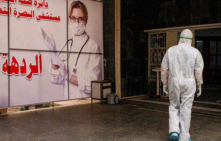 A medical worker is seen at Basra University Hospital, in southern Iraqi, on April 1, 2020. Iraq's media regulator recently suspended Reuters' license for three months over a report on the COVID-19 pandemic. (AFP/Hussein Faleh)