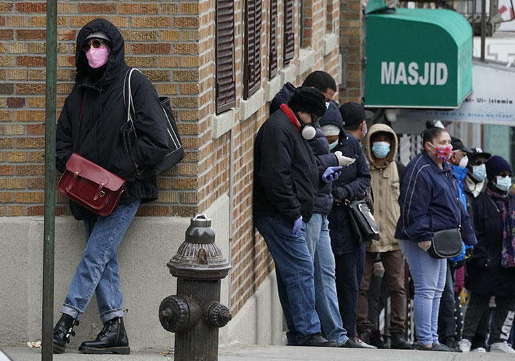 People wait in line for a coronavirus test at a new walk-in testing sites that opened in the parking lot of NYC Health + Hospitals/Gotham Health Morrisania in the Bronx section of New York on April 20, 2020. Photographers in New York and around the U.S. have had to navigate a new reality under COVID-19. (AFP/Timothy A. Clary)