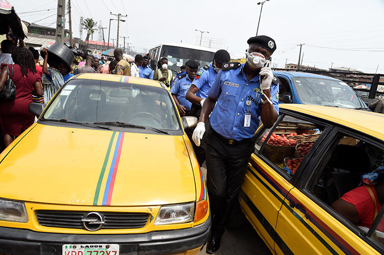 A police officer is seen in Lagos, Nigeria, on March 26, 2020. Police recently arrested two journalists for their work in Ebonyi state. (AFP/Pius Utomi Ekpei)