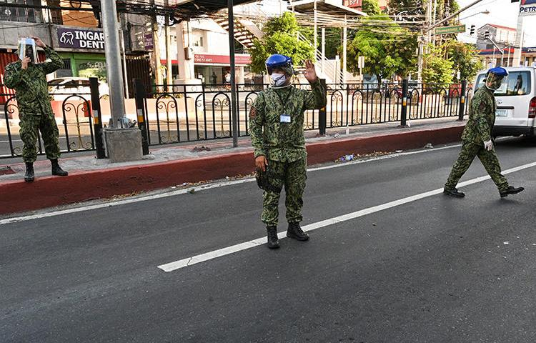 Police officers are seen in Manila, the Philippines, on March 25, 2020. National police recently filed a criminal complaint on behalf of Cavite City authorities against two journalists for spreading 'false information' about COVID-19. (AFP/Ted Aljibe)