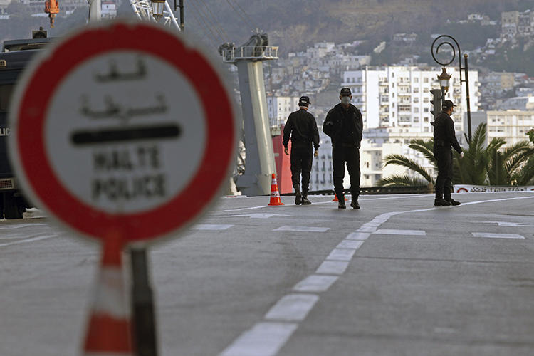 """Security forces are seen in Algiers, Algeria, on April 8, 2020. Algerian authorities recently blocked three news websites in the country and passed legislation criminalizing """"fake news."""" (AP/Toufik Doudou)"""