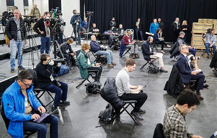 New York'ta, 24 Mart 2020 günü, COVID-19 salgını tedbirleri dahilinde geçici hastaneye dönüştürülecek olan Jacob Javits Merkezi'nde gazeteciler New York Valisi Andrew  Cuomo'nun konuşmasını sosyal mesafeyi koruyarak izliyorlar. (AP Photo/John Minchillo)
