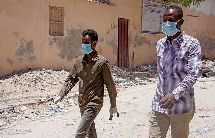 Men are seen in Mogadishu, Somalia, on March 18, 2020. Somali authorities recently arrested journalist Abdiaziz Ahmed Gurbiye over his COVID-19 Facebook posts. (AP/Farah Abdi Warsameh)