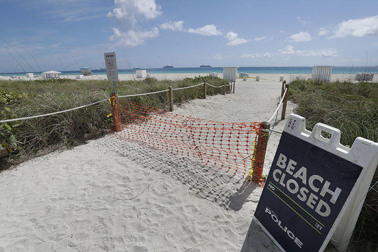An entrance to a beach is closed on March 31, 2020, in Miami Beach, Florida. (AP Photo/Wilfredo Lee)