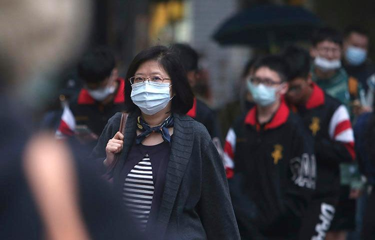 People walk on a street in Taipei, Taiwan, on March 30, 2020. CPJ recently spoke with journalist Brian Hioe on covering COVID-19 in Taiwan. (AP/Chiang Ying-ying)