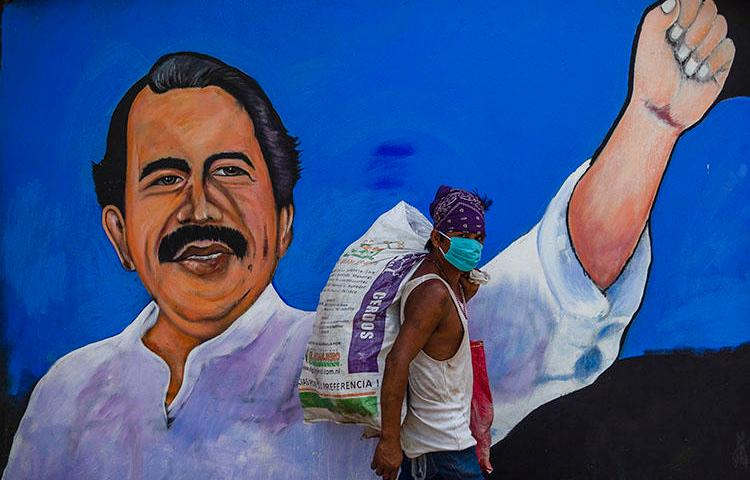 A homeless man wears a face mask against the spread of COVID-19 as he walks past a mural depicting Nicaraguan President Daniel Ortega, in Managua on April 9, 2020. Journalist Álvaro Navarro recently described to CPJ his experiences covering the pandemic in Nicaragua. (AFP/Inti Ocon)