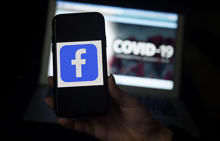 The Facebook logo is displayed on a mobile phone screen photographed on a COVID-19 illustration graphic background on March 25, 2020 in Arlington, Virginia. CPJ and partners called on social media and content sharing platforms to preserve data amid the pandemic. (AFP/Olivier Douliery)