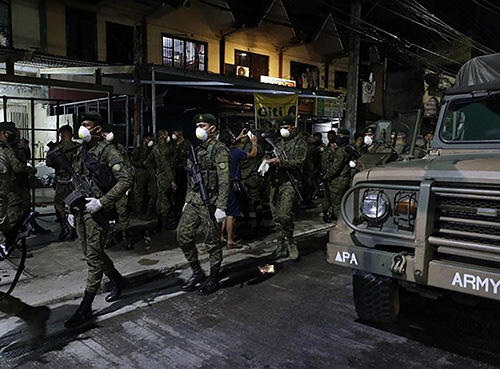 """Soldiers wear masks in the Philippines, where the government has imposed criminal penalties for spreading """"false news"""" about the pandemic. (AP/Aaron Favila)"""