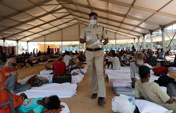 A police officer walks inside a shelter set up for migrants in Mumbai, India, April 6, 2020. The Indian Supreme Court recently passed a directive in response to alleged fake news that prompted migration in the country. (Reuters/Francis Mascarenhas)