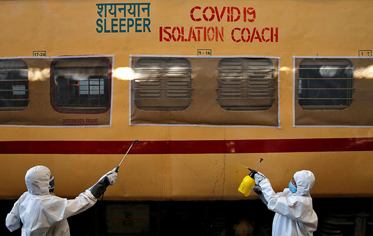 Workers wearing protective suits disinfect a passenger train on the outskirts of Kolkata, India, on April 6, 2020. Indian freelance journalist Vidya Krishnan recently spoke with CPJ about the challenges of covering the COVID-19 pandemic. (Reuters/Rupak De Chowdhuri)