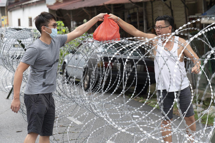 A man collects supplies over barbed wire in the coronavirus lockdown area of Selayang Baru, outside of Kuala Lumpur, Malaysia, on April 26, 2020. A journalist faces prison time over her social media posts on the health crisis. (AP/Vincent Thian)