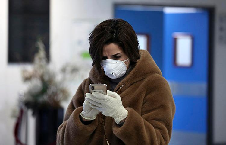 Jornalista libanesa usa o telefone celular usando máscara e luvas descartáveis no Hospital Universitário Rafik Hariri em Beirute, Líbano, em 22 de fevereiro de 2020. (AP/Bilal Hussein)
