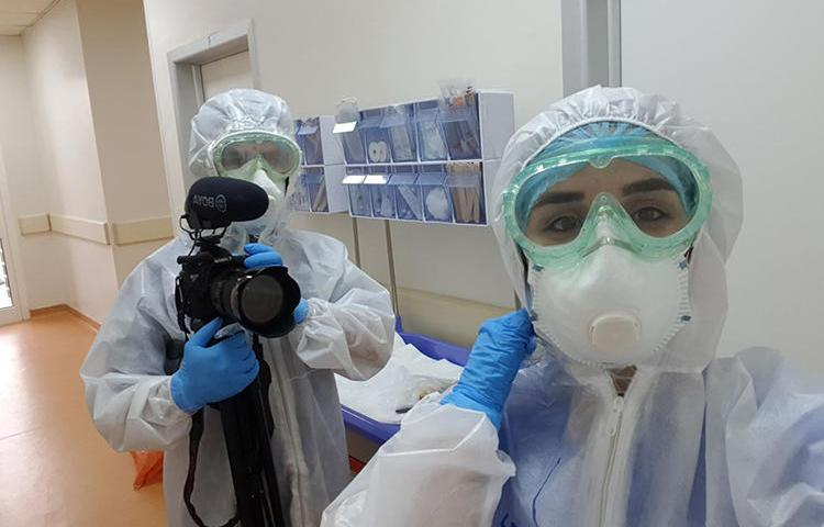 Freelance photographer and videographer Zmnako Ismael (left) is seen covering the COVID-19 pandemic. (Photo via Ismael)