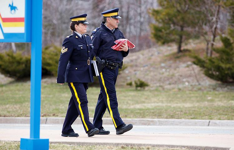 Two Royal Canadian Mounted Police (RCMP) officers leave the Nova Scotia RCMP Headquarters in Dartmouth, Nova Scotia, on April 20. Journalists in the province have struggled to cover a mass shooting due to COVID-19 containment measures. (Reuters/John Morris)