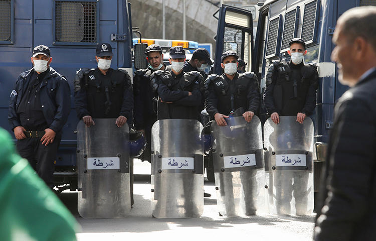Police officers wearing face masks stand guard during an anti-government protest, following the coronavirus outbreak, in Algiers, Algeria on March 6, 2020. News websites covering both the unrest and the impact of the disease have recently been blocked in the country. (Reuters/Ramzi Boudina)