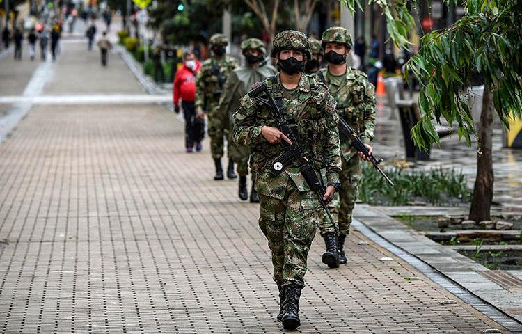 Soldados colombianos que llevan mascarillas como medida preventiva contra la propagación del COVID-19 se despliegan en la plaza Simón Bolívar en Bogotá el 21 de abril de 2020. Un informe del semanario colombiano Semana publicado el 1 de mayo reveló que oficiales de la inteligencia militar colombiana había espiado a periodistas locales e internacionales. (AFP/Juan Barreto)