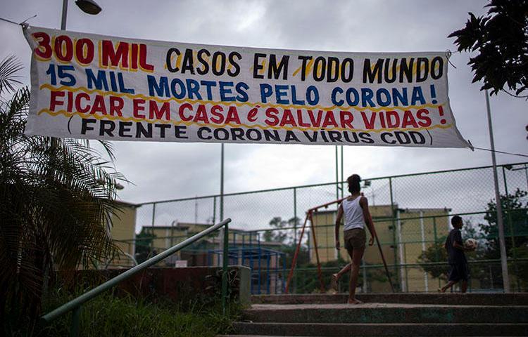 """Um banner dizendo """"300milasos em todo mundo, 15 mil mortes pelo corona! Ficar em casa é salvar vidas!"""" pendurado na Cidade de Deus, favela do Rio de Janeiro, em 7 de abril de2020, durante a pandemia de COVID-19. Os jornalistas comunitários doRioenfrentan desafios diários para informar os moradores sobre a COVID-19. (AFP/Mauro Pimentel)"""