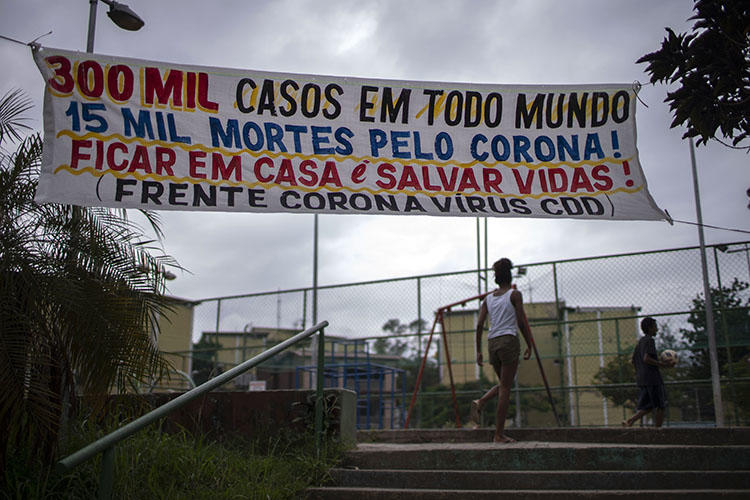 "A banner reading ""300,000 cases in the world, 15,000 deaths because of coronavirus! Stay at home and save lives!"" hangs at the Cidade de Deus favela in Rio de Janeiro, Brazil, on April 7, 2020, during the COVID-19 outbreak. Rio's community journalists face daily challenges informing favela residents about COVID-19. (AFP/Mauro Pimentel)"