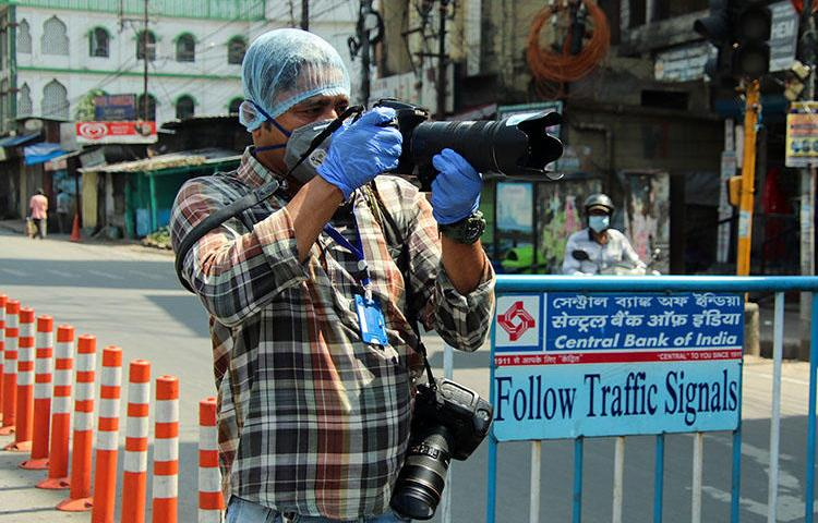 El fotógrafo de la AFP, Diptendu Dutta, trabaja durante una cuarentena impuesta por el gobierno como medida preventiva contra el contagio de COVID-19 en Siliguri, en la India, el 10 de abril del 2020. Periodistas freelance han arriesgado sus vidas y su ingreso en el contexto de la pandemia del COVID-19. (AFP)