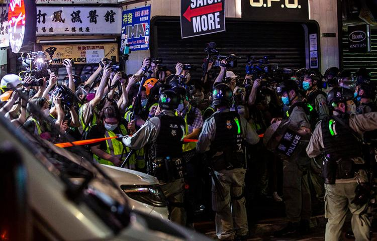 Riot police hold back members of the press in the Mong Kok district of Hong Kong on May 10, 2020. Police attacked and arrested journalists covering that protest. (AFP/Isaac Lawrence)
